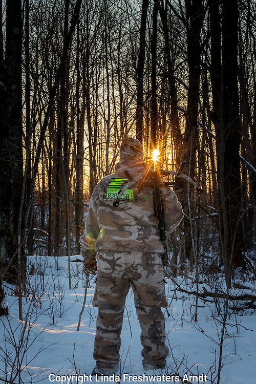 Crossbow hunter walking into the sunset