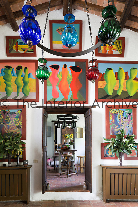 The sitting room with paintings by South African artist Nicolaas Maritz. Traditional local materials were kept during the restoration of the house, such as the terracotta tiles on the floor and ceilings and the original massive wooden beams.