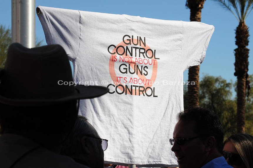 "Phoenix, Arizona. January 19, 2013 - Demonstrators in Phoenix display a T-shirt expressing their views on gun control in America. As President Barack Obama proposed new gun regulations last week, gun owners demonstrated against it with national ""Guns Across America"" rallies to defend the Second Amendment. Dozens showed up at the Arizona State Capitol, many of them carrying weapons. Photo by Eduardo Barraza © 2013"