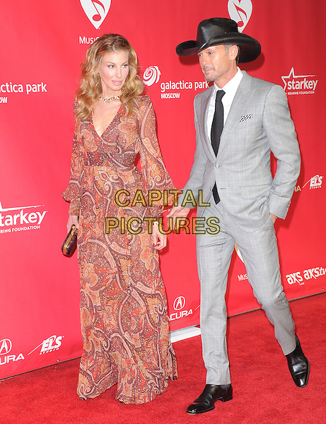 Faith Hill and Tim McGraw.The MusiCares 2013 Person Of The Year Tribute held at The Los Angeles Convention Center, West Hall in Los Angeles, California, USA..February 8th, 2013.full length long sleeve dress clutch bag brown print gold red necklace patterned hat black tie grey gray suit married husband wife  .CAP/RKE/DVS.©DVS/RockinExposures/Capital Pictures.