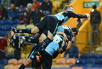 Wycombe Wanderers Jason McCarthy jumps on Aaron Amadi-Holloway and Luke O'Nien after the substitute sealed the victory with their second goal during the Sky Bet League 2 match between Mansfield Town and Wycombe Wanderers at the One Call Stadium, Mansfield, England on 31 October 2015. Photo by Garry Griffiths.