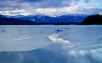 Idaho, North, Bonner County, Sandpoint. Ice thaws on Oden Bay of Lake Pend Oreille. Schweitzer Mountain in the distance.