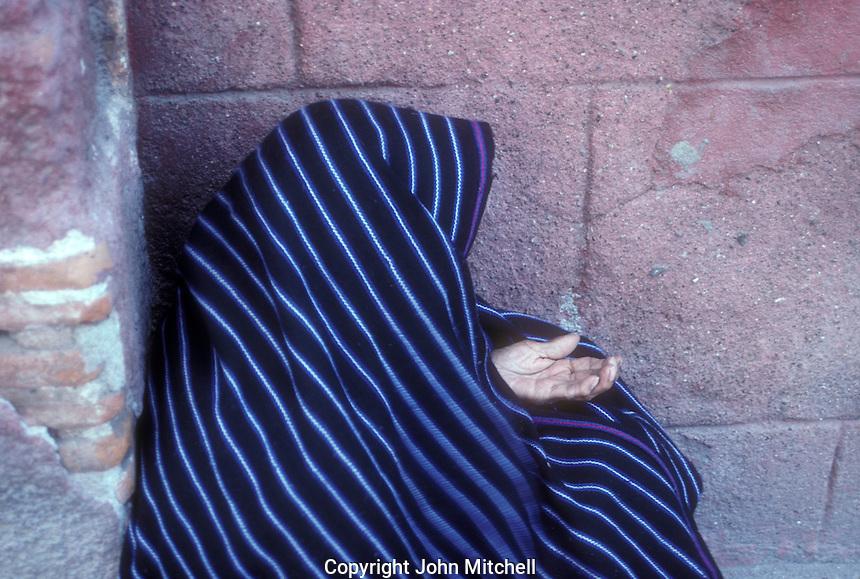 Elderly woman wearing a woven Mexican rebozo begging on the street in San Miguel de Allende, Mexico