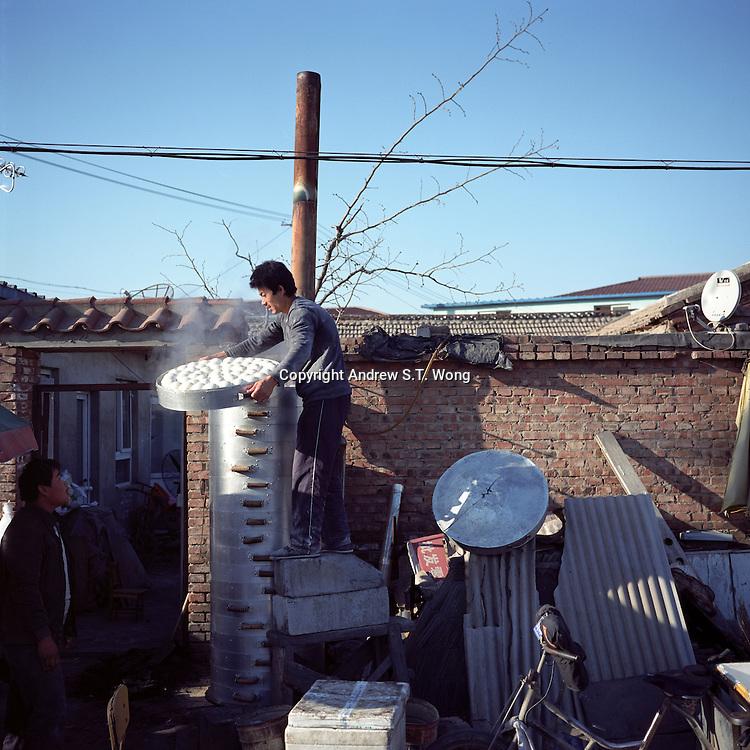 A man steams Chinese buns at a village on the outskirts of Beijing, China in November, 2010. (Mamiya 6, 75mm f3.5, Kodak Ektar 100 film)