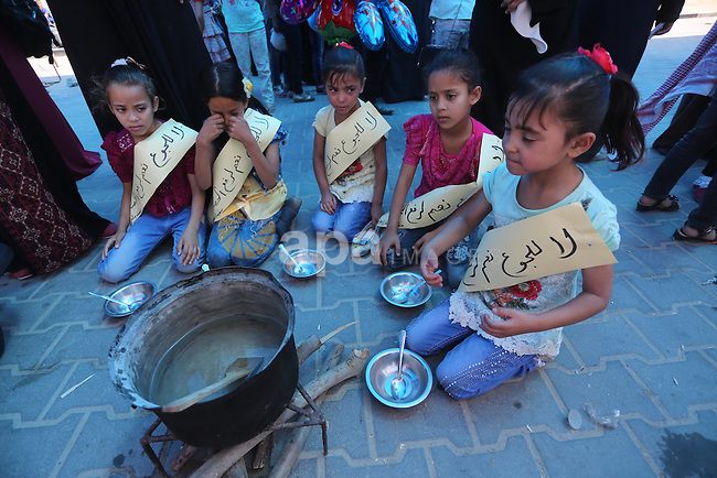 Palestinian children hold banners during a protest to break the siege, at the seaport of Gaza City on 01 June 2016. Photo by Mohammed Asad