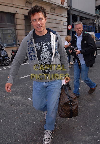JOHN BARROWMAN .Seen outside the BBC Radio 2 building, London, England, UK, .September 4th 2009..full length jeans denim brown bag holdall trainers grey gray hoodie photographer .CAP/IA.©Ian Allis/Capital Pictures