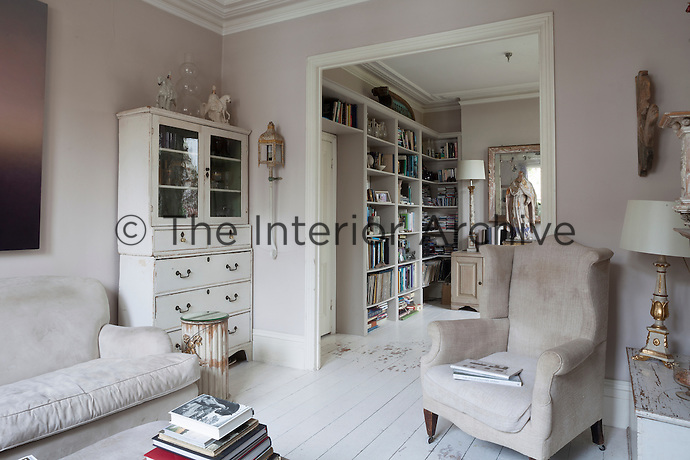 An antique chest of drawers and seperate cabinet have been made into a single storage unit in a corner of the living room