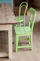 Mismatched brightly painted kitchen chairs line the rustic wooden table in the kitchen