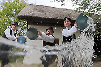 Local young men splash water at women as part of the traditional folklore Easter celebration during a press event in the Skanzen open air ethnographic museum in Szentendre (about 20 km North of capital city Budapest), Hungary on April 22, 2019. ATTILA VOLGYI