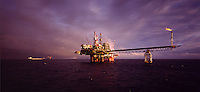 North Sea. Oil production platform with tanker loading from linked loading column in the background.  Evening..