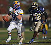 Anthony LaRosa #10, East Meadow quarterback, left, looks for an open receiver as Baldwin #32 Isaiah Dennis moves in for a sack during the third quarter of the Nassau County varsity football Conference I quarterfinals at Baldwin High School on Saturday, Nov. 5, 2016. Baldwin won by a score of 35-8.