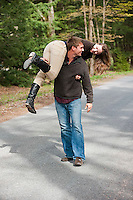 Young man giving piggy back ride to young woman on road