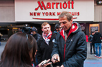 U.S. men's head coach Jurgen Klinsmann signs an autograph for a fan during the centennial celebration of U. S. Soccer at Times Square in New York, NY, on April 04, 2013.