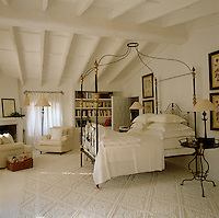 An antique wrought-iron canopy bed dominates this white bedroom