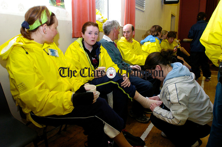 Niamh Frawley helps Mary Eustace of Kildysart her foot bandage during the can Clare 250 mile cycle at Mullagh hall.  Photograph by John Kelly.
