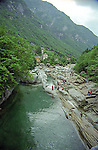 The blue green Ticino River flows slowly past visitors on an eroded rocky playground.