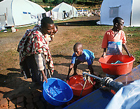 A Rwandan patient and orphan residents of the AmeriCares clinic draw bath and laundry water from a water holding bladder in the Buranga Rwanda clinic compound in Oct., 1994. Refilled daily with treated water, the bladder and another each holding about 200 gallons supplied three inpatient tents of 10-15 people each as well as a tent which was temporary home to about 15 orphans.  The New Canaan, Conn.,  humanitarian organization ran the clinic from August to Dec., 1994 to help refugees returning from camps in Goma, Zaire (now Congo). The clinic also treated any who came for help with many problems, frequently related to the collapse of infrastructure which provided for basic needs. The country was ravaged by genocide and civil war in 1994.