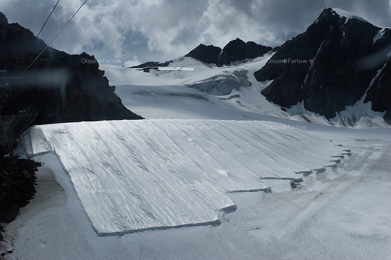 A view from below shows how futile are the efforts of covering Brunnenkogel Ferner.  The glacier is wrapped with a fleece-like cover to keep it from melting. Covered ice melts slower. <br /> The ski area at 3,400 meters is covered to help save the ski industry since the glacier is retreating.  The cost of materials is one Euro per square meter.<br /> <br /> The Alpine glaciers -- in Austria, Switzerland, France and Italy -- are losing one percent of their mass every year and, even supposing no acceleration in that rate, will have all but disappeared by the end of the century. More hot, dry summers like that of 2003 in Europe, when the loss speeded to five percent, could cut the life expectancy to no more than 50 years, according to Wilfried Haeberli of the University of Zurich. &quot;We estimate that by the end of the 21st century, with a medium-type climate scenario, about five percent of what existed in the 1970s will have survived, he added.