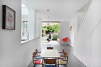 A set of designer dining chairs with coloured seats are arranged around a simple breakfast table in a minimalist room. A red Eames chair in the corner provides a spot of colour against the white wall. Owner Jimi Lee sits on the deck beyond.