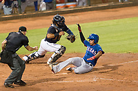 AZL Rangers pinch runner Yenci Pena (18) slides to avoid the tag by catcher Felix Fernandez (17) as home plate umpire Glen Meyerhofer during an Arizona League playoff game against the AZL Indians 1 at Goodyear Ballpark on August 28, 2018 in Goodyear, Arizona. The AZL Rangers defeated the AZL Indians 1 7-4. (Zachary Lucy/Four Seam Images)