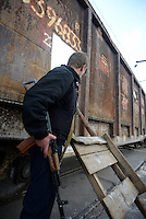 A Pro-Russian activist holding a machine gun at a railroad checkpoint. Slavyansk, Donetsk region.