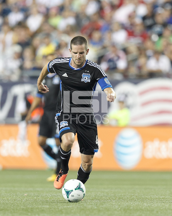 San Jose Earthquakes midfielder Sam Cronin (4) brings the ball forward.  In a Major League Soccer (MLS) match, the New England Revolution (white) defeated San Jose Earthquakes (black), 2-0, at Gillette Stadium on July 6, 2013.