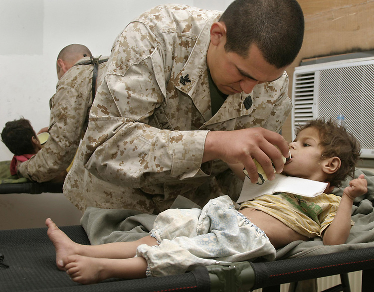 AL ASAD, Iraq (June 8, 2005) - Hospital Mate 2 Douglas Ayala assists a malnourished Iraqi boy drink Gatorade. The boy was found in Dhulab by Marines from 2nd Marine Regiment, 3rd battalion, Lima Company. The Marines of 2d Marine Division conduct counter-insurgency operations with Iraqi Security Forces to isolate and neutralize Anti-Iraqi Forces, to support the continued development of Iraqi Security Forces, and to support Iraqi reconstruction and democratic elections in order to create a secure environment that enables Iraqi self-reliance and self-governance. (Official USMC photo by LCpl. Shane S. Keller)