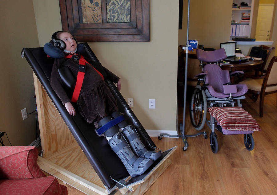Sandra Massart, 10, listens to stories recorded in her father William Massart's voice at the family's apartment in Durham, NC, USA, on Tuesday, Feb. 14, 2012.  Sandra Massart is being treated at Duke University Hospital in Durham, NC, for MLD, a degenerative condition.  Photo by Ted Richardson