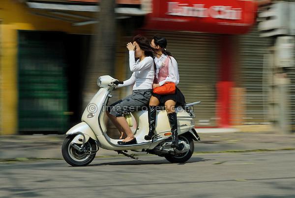 Asia, Vietnam, Hanoi. Hanoi old quarter. Two women on Vespa motorbike rushing through Hanoi.