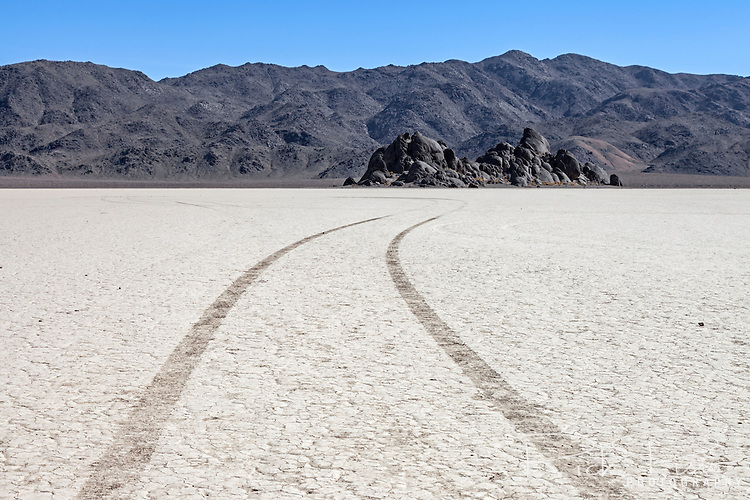 Tier tracks scar the fragile floor near the Grandstands on the Racetrack Playa in Death Valley National Park