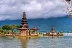 "The Hindu temple of Ulun Danu at Candikuning is one of the iconic images of Bali, Indonesia.  Located in the high hills of the Bedugul, about 30 miles north of Bali's capital city of Denpasar, the temple is built on the shores of the crater Lake Bratan (formed from the sunken crater of a long-dormant volcano).  Much of the inner precincts of the temple is closed to the (non-Hindu) public, but the gardens are spectacular and feature fabulous shrines, statuary, and views.  The iconic tourist image is the two ""water shrines,"" which these days are usually partially submerged in the waters of Lake Bratan.  (HDR Image)"