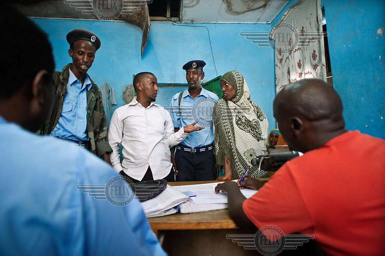 A policeman takes notes as people accuse each other in an argument at a police station in Mogadishu.