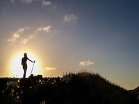 The silhouette of a woman hiking at sunset at Ka'ena Point, West O'ahu.