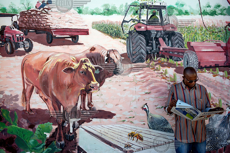 A man reads a newspaper in front of a mural of an agricultural scene at the Ministery of Agriculture.