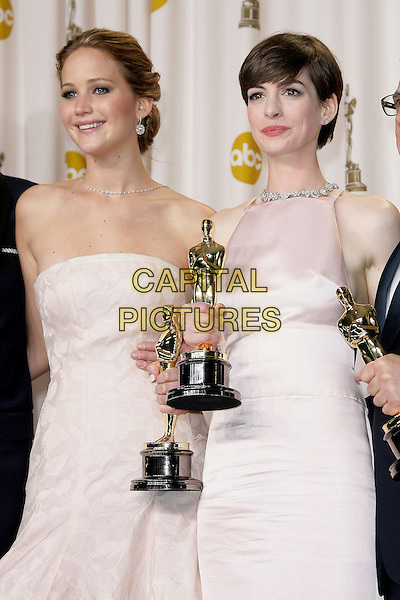 Jennifer Lawrence, Anne Hathaway .85th Annual Academy Awards held at the Dolby Theatre at Hollywood & Highland Center, Hollywood, California, USA..February 24th, 2013.pressroom oscars half length white award trophy trophies winner winners white pink pale strapless dress trophies winners .CAP/ADM.©AdMedia/Capital Pictures.