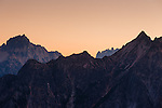 Salmon-colored light fills the hazy atmosphere around Tower Mountain and the surrounding mountains in Washington's North Cascade mountain range.