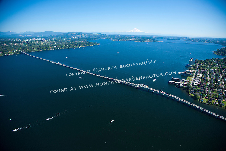 An aerial view of boats and the Highway 520 floating bridge, also known as the Evergreen Point Floating Bridge, crossing Lake Washington from Seattle (near shore) to Medina, Bellevue, and the Eastside (far shore) with Mt. Rainier in the background.