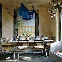 A blue paper mobile in the shape of a bird hangs above a laid table in front of a hand-painted mural in this kitchen/dining room