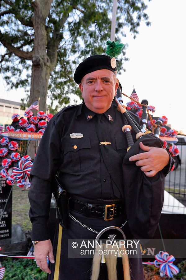 Merrick, New York, USA. September 11, 2015. KEViN MAC CARTAIGH of Massapequa, a member of NYPD Pipe Band, stands in front of monument at Merrick Memorial Ceremony for Merrick volunteer firefighters and residents who died due to 9/11 terrorist attack at NYC Twin Towers. Ex-Chief Ronnie E. Gies ,of Merrick F.D. and FDNY Squad 288, and Ex-Captain Brian E. Sweeney, of Merrick F.D. and FDNY Rescue 1, died responding to the attacks on September 11, 2001.
