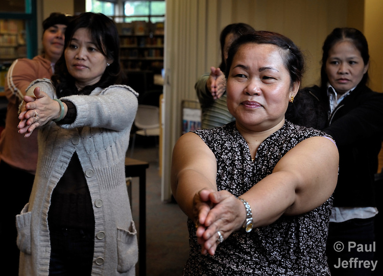 Recently arrived women immigrants from different parts of the world learn stretching and exercise techniques during a class sponsored by Tacoma Community House in Tacoma, Washington. Held at a public library, the class also serves as one more medium in which the women can learn and practice English. TCH is a mission institution sponsored by United Methodist Women.