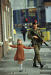 Ireland The Troubles. Belfast 1980s. Girl skipping with British Army soldier patrolling the streets.