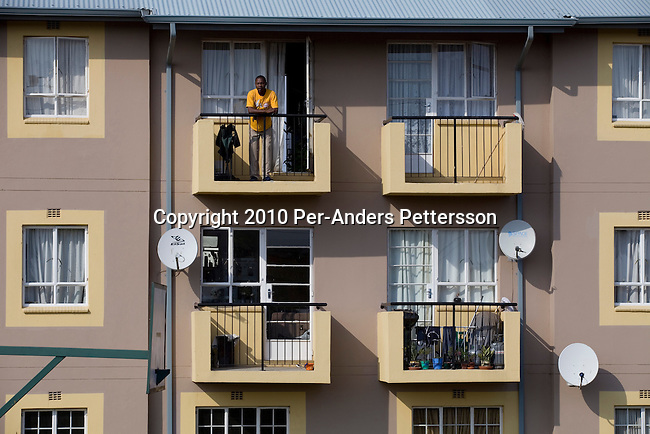 SOWETO, SOUTH AFRICA - JANUARY 15: A man stands on his balcony of a newly constructed security complex on January 15, 2010, in the Kliptown section of Soweto, South Africa. Soweto is the largest township in South Africa, located about 10 kilometers southwest of downtown Johannesburg. The population is estimated to be around 2-3 million. A growing black middle class can be seen in the township and many shopping malls and has been built the last few years. (Photo by Per-Anders Pettersson/Getty Images)