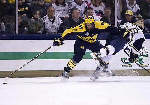 February 08, 2013:  Michigan forward Cristoval 'Boo' Nieves (12) and Notre Dame defenseman Stephen Johns (28) battle for the puck during NCAA Hockey game action between the Notre Dame Fighting Irish and the Michigan Wolverines at Compton Family Ice Arena in South Bend, Indiana.  Notre Dame defeated Michigan 7-4.
