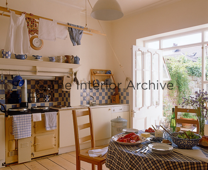 A light and airy country-style kitchen has an Aga at its centre and a blue and white theme