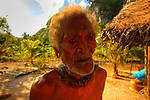 Local elderly man in a fishermen village at.Panasia Island.Panasia is a spectacular island of uplifted coral reef making jagged limestone cliffs in the Louisiade Archipelago..The Louisiade Archipelago is a string of ten larger volcanic islands frequently fringed by coral reefs, and 90 smaller coral islands located 200 km southeast of New Guinea, stretching over more than 160 km and spread over an ocean area of 26,000 km  between the Solomon Sea to the north and the Coral Sea to the south. The aggregate land area of the islands is about 1,790 kmu178  (690 square miles), with Vanatinai (formerly Sudest or Tagula as named by European claimants on Western maps) being the largest..Sideia Island and Basilaki Island lie closest to New Guinea, while Misima, Vanatinai, and Rossel islands lie further east..The archipelago is divided into the Local Level Government (LLG) areas Louisiade Rural (western part, with Misima), and Yaleyamba (western part, with Rossell and Tagula islands. The LLG areas are part of Samarai-Murua District district of Milne Bay. The seat of the Louisiade Rural LLG is Bwagaoia on Misima Island, the population center of the archipelago. .The Louisiade Archipalego is part of the Milne Bay province of Papua New Guinea..It lies between approximately 10 degrees south and 11.5 degrees south, and 151 degrees east and 154 degrees east. It is an area of Islands, reefs and cays some 200 nm long and 50 nm wide, stretching from the south east tip of mainland Papua New Guinea in a east south east direction..Panasia Island.Panasia is a spectacular island of uplifted coral reef making jagged limestone cliffs in the  Louisiade Archipelago..The Louisiade Archipelago is a string of ten larger volcanic islands frequently fringed by coral reefs, and 90 smaller coral islands located 200 km southeast of New Guinea, stretching over more than 160 km and spread over an ocean area of 26,000 km  between the Solomon Sea to the north and the Coral Sea to the south. The aggregate lan