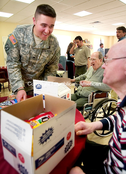 PROSPECT, CT. 05 April 2007-040507SV01--From left, Jeremy Mack, 19, of New Milford, a medic in the Army, packs up supplies and gifts that he will bring back to Iraq with him. World War II vets, Army Corporal Francis Daly and Army Tec. Sgt. Warren Gould help him pack the items at Marathon Health Care in Prospect Thursday.<br /> Steven Valenti Republican-American
