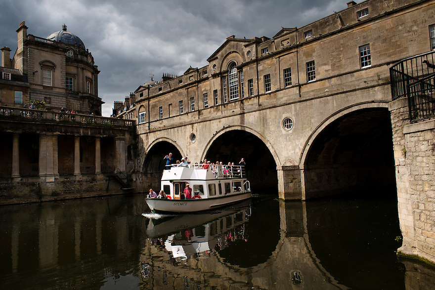 A pleasure boat passing under Pulteney Bridge, Bath, UK, August 16, 2015. The UNESCO World Heritage city of Bath is famed for its hot spa that dates back to Roman times and for its Georgian architecture. For much of its history the city has been a popular holiday resort. It is the only hot spa in the UK.