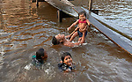With help from her father, an indigenous girl jumps into the Javari River at Atalaia do Norte in Brazil's Amazon region.
