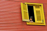 BUENOS AIRES - FEBRUARY 12: A small girl looks out of a window in the La Boca neighborhood of Buenos Aires, Argentina on February 12, 2009.