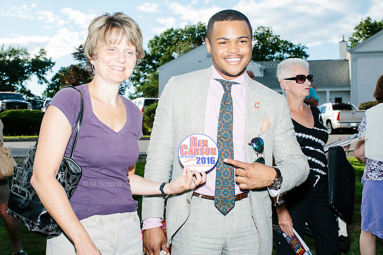 People hold a campaign sticker as they take photos after meeting Republican presidential candidate Dr. Ben Carson at Londonderry Old Home Day in Londonderry, New Hampshire.